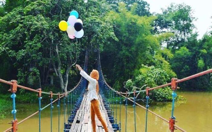 Jembatan gantung di punti kayu, melintas di atas lintasan perahu naga