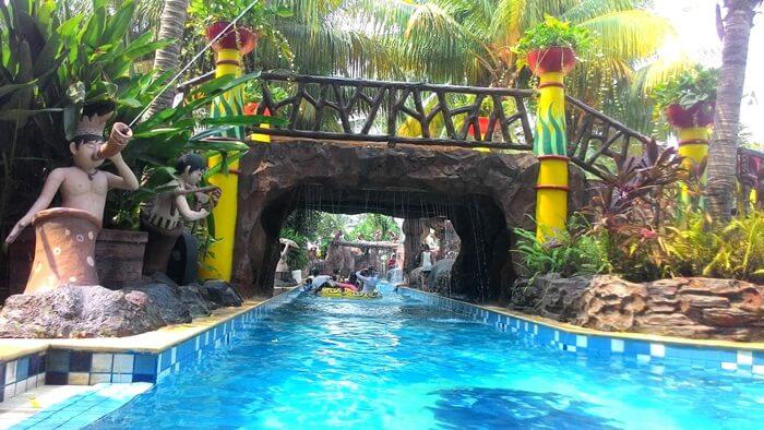 Kolam Arus dengan pemandangan pancuran dan patung warna warni di sepanjang tepi alurnya.