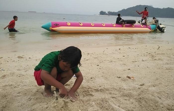 Main pasir di pantai mutun berdampingand negan perahu untuk banana boat
