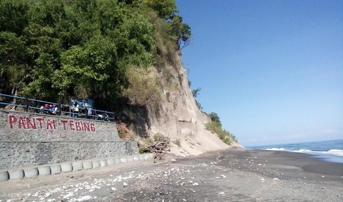 Leter nama Pantai Tebing tertulis di tembok penahan abrasi.