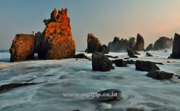 Saat Pagi menyinari karang dengan sudut rendah di pantai gigi hiu