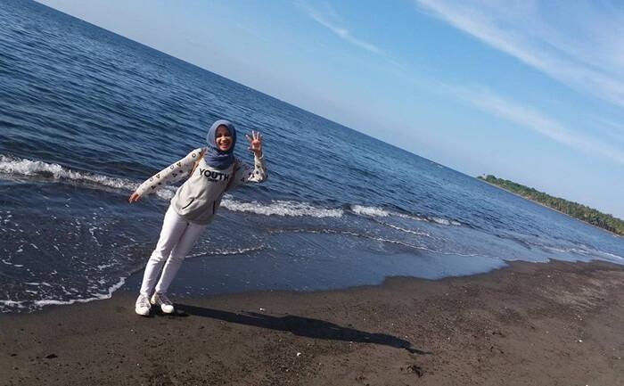 berpose cantik di atas pasir htam pantai tebing lombok