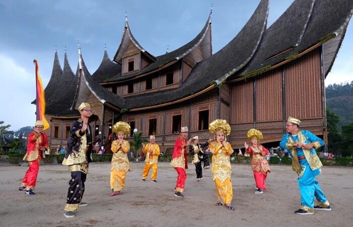 Berfoto dengan pakaian Minang di depan istana pagaruyung