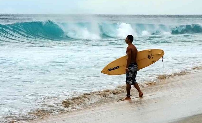 surfing di pantai setangi banyak diminati surfer pemula, terutama anak anak lokal yang sedang belajar