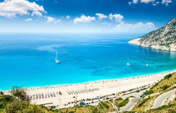 Terletak di utara-barat dari Kefalonia, pantai Myrtos adalah tempat wisata di Yunani yang populer karena warna magis airnya