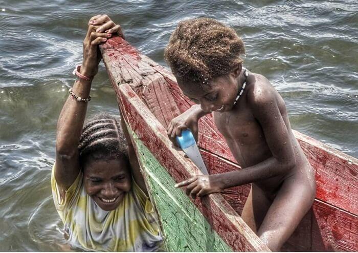 Anak-anak [enduduk lokal tampak santai bermain di danau Rombebai.