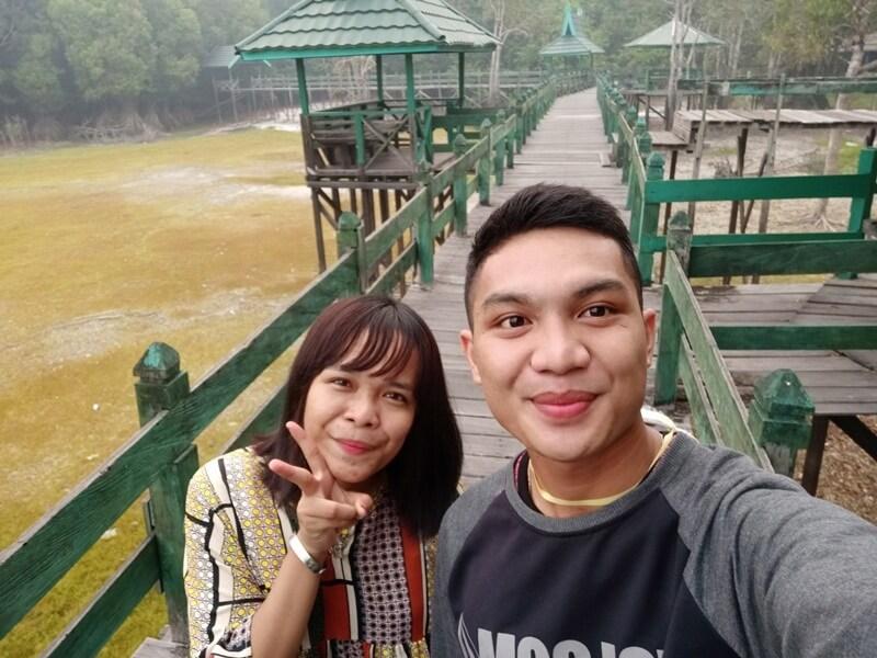 berfoto di jembatan kayu