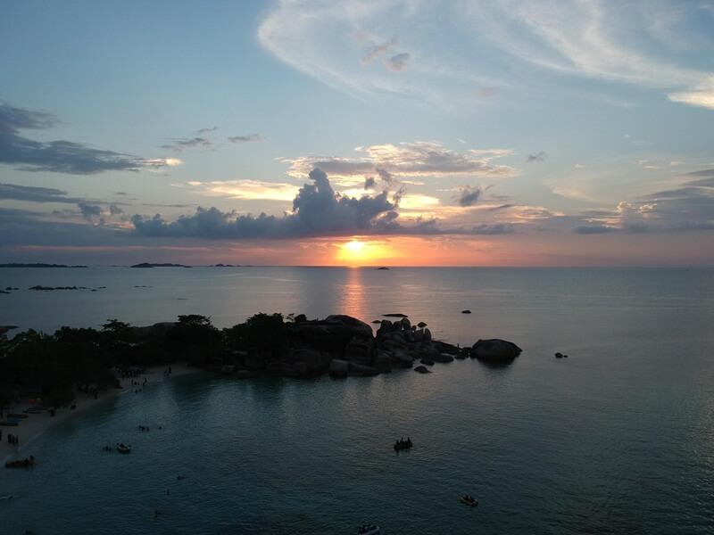 matahari terbenam di pantai tinggi tanjung